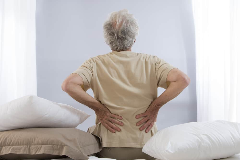 Senior man holding lower back pain treatment active approach to recovery Propel Physiotherapy